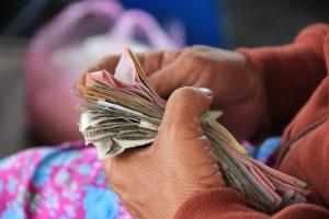 Ett par händer håller i en bunt med sedlar