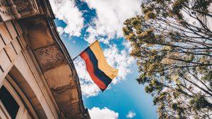 Den Colombianska flaggan vajar högst upp på ett hus, i backgrunden ser man en blå himmel med vita moln
