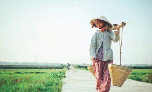 En asiatisk kvinna bär på hinkar och har hatt