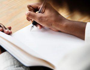 Närbild på en hand som skriver i ett block