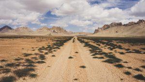 En torr väg syns, i bakgrunen syns sand och klippiga berg