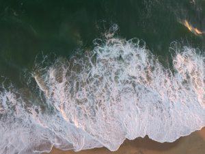 Foto på vågor vid en strand som fotograferats uppifrån