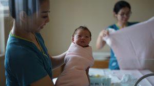En bebis hålls upp av vårdpersonal