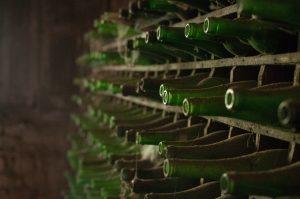 Gröna glasflaskor uppradade i ett hyllplan i en källare