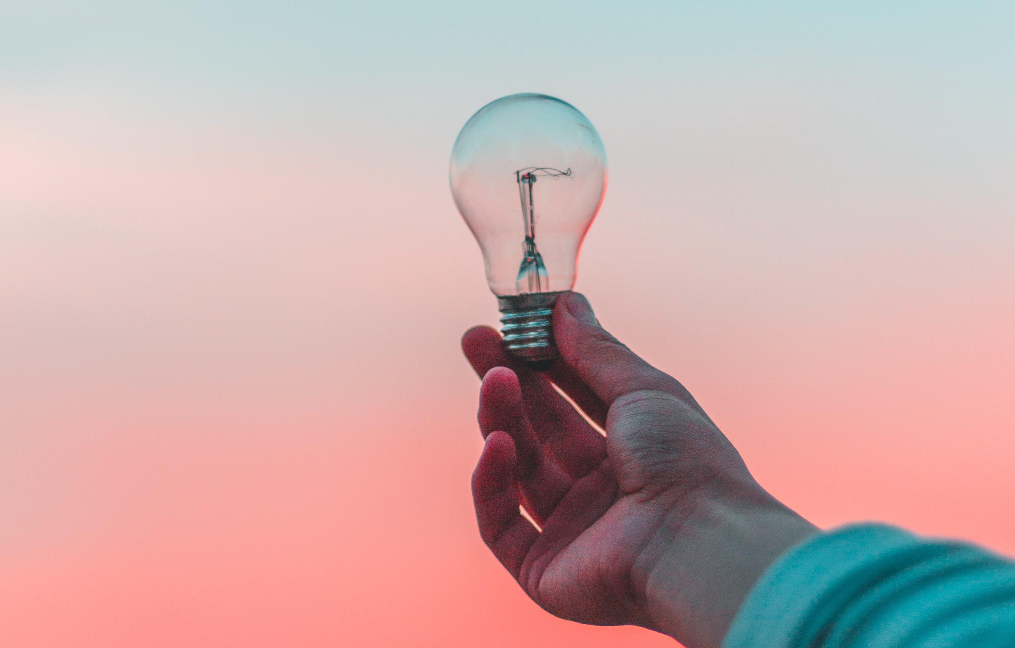 En hand håller upp en glödlampa mot en rosa himmel