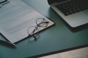 Ett par runda svarta glasögon ligger på ett skrivbord, med ett papper och en datorn