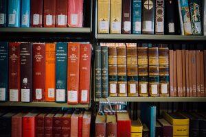 Gamla böcker i olika storlek och färger står uppradade i en bokhylla