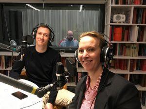 Två podcastdeltagare i inspelningsstudion med hörlurar och mikrofoner