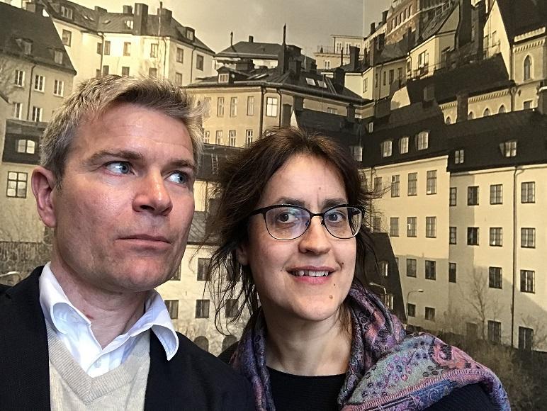 Två podcastdeltagare står framför en tapet med husfasader