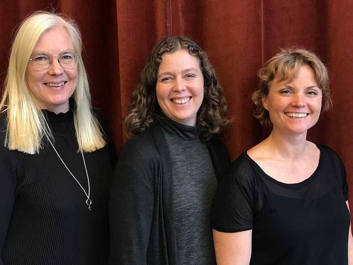 Tre podcastdeltagare ler mot kameran och står framför en röd sammetsgardin