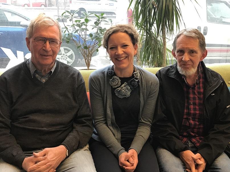 Tre podcastgäster sitter i en soffa, i bakgrunden är ett fönster ut mot gatan där bilar står parkerade