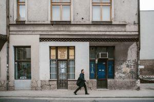 En man i rock går på en trottoar framför en grå sliten fasad