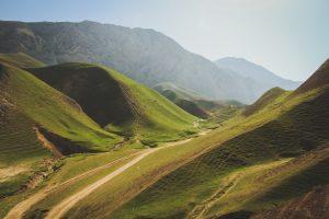 Foto på en dal bland grönda berg. En solig himmel syns i bakgrunden