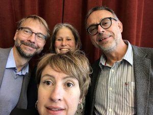 Tre podcastdeltagare och programledare tittar in i kameran