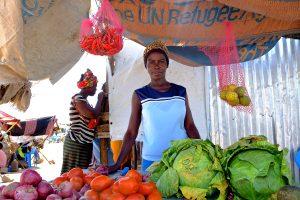En kvinna som säljer grönsaker på en marknad tittar in i kameran. Framför henne ligger sallandshuvuden, tomater och lök