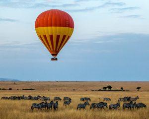 En luftballong flyger över savannen med zebror