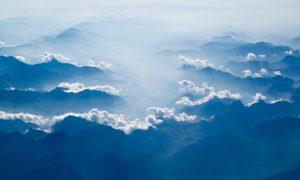 Foto på klippiga berg, ovanför svävar lätta vita små moln. Man ser långt bort i horisonten, överallt sträcker sig syns berg och moln
