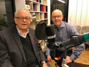 Göran Hydén och Joakim Molander sitter i poddstudion. En mikrofon syns.