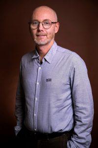 Porträttbild av Joakim Molander, framför en brun enfärgad bakgrund